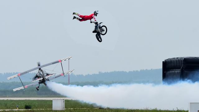 摩托車飛躍正在低飛的Pitts飛機
