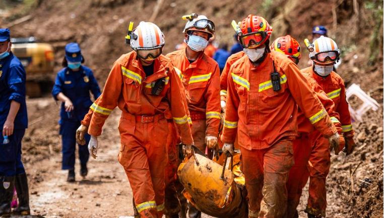 救援人員從山體滑坡現場運出遇難者遺體